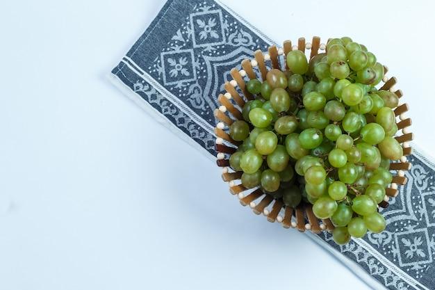 Uvas verdes em uma cesta plana sobre fundo branco e toalha de cozinha