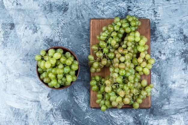 Uvas verdes em uma tigela plana colocadas em gesso sujo e fundo de placa de corte