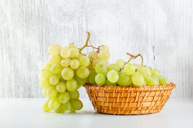 Uvas verdes em uma vista lateral de cesta de vime em branco e sujo