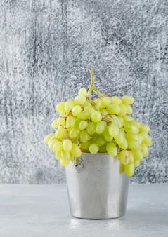 Uvas verdes em uma vista lateral de mini balde em gesso e cinza sujo