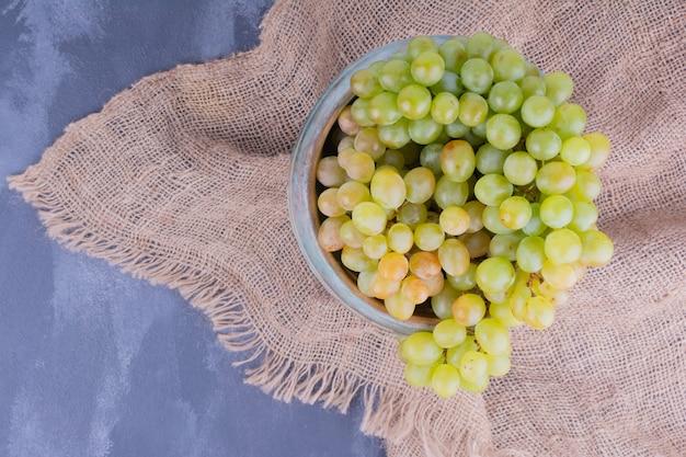 Uvas verdes em uma xícara rústica na superfície azul
