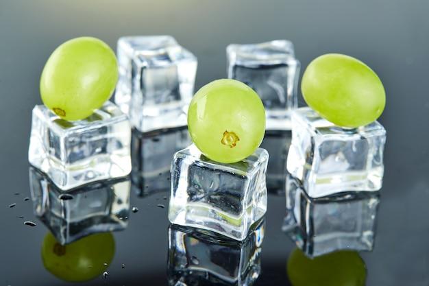 Uvas verdes frescas com gotas de água e cubos de gelo no fundo cinzento