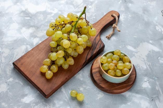 Uvas verdes frescas com mesa marrom na luz