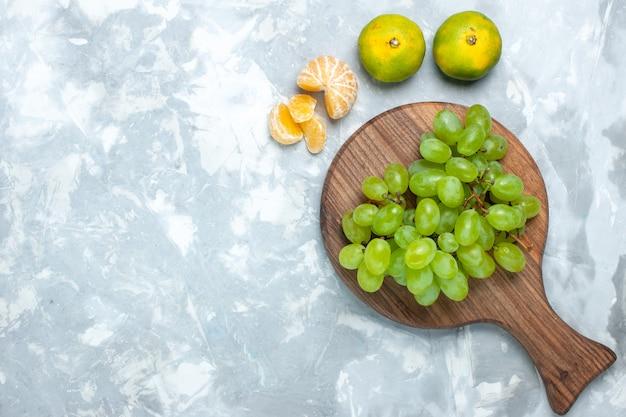 Uvas verdes frescas de vista superior frutas suculentas maduras com tangerinas na mesa de luz.