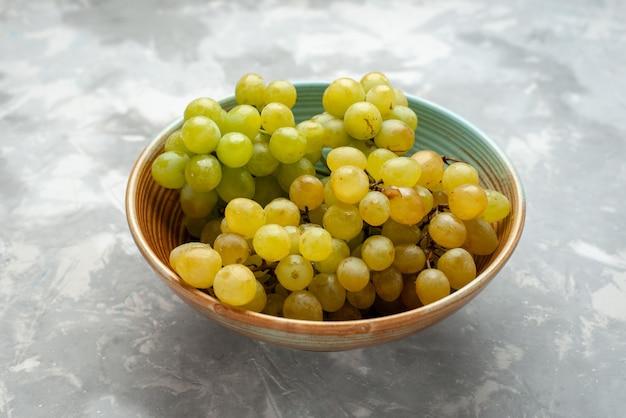 Uvas verdes frescas dentro do prato na luz
