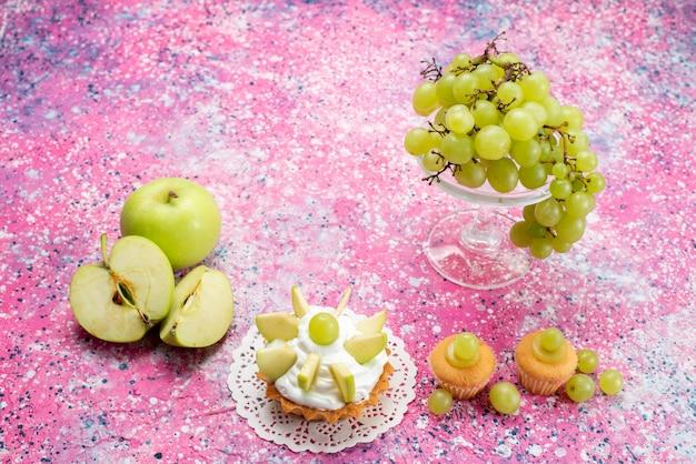Uvas verdes frescas e frutas totalmente azedas e deliciosas com bolinhos na luz