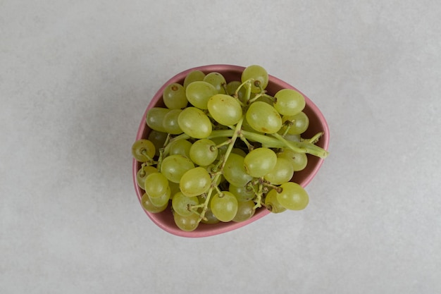 Uvas verdes frescas em tigela rosa