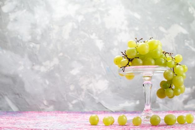 Uvas verdes frescas inteiras azedas e frutas deliciosas na luz