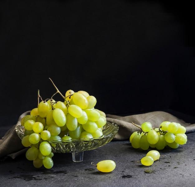 Uvas verdes maduras frescas em uma fruteira de vidro em fundo preto. copie o espaço