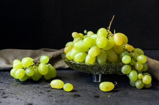 Uvas verdes maduras frescas em uma fruteira de vidro em fundo preto