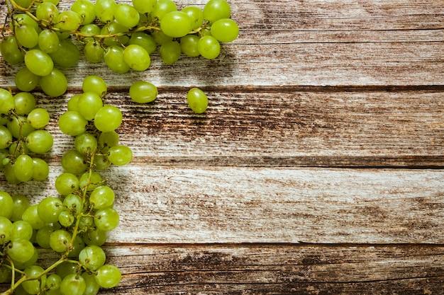 Uvas verdes maduras frescas na mesa de madeira marrom