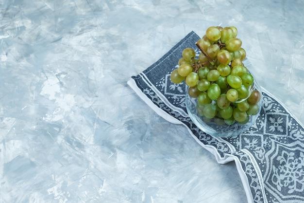 Uvas verdes planas em vaso de vidro em fundo cinza sujo e toalha de cozinha. horizontal