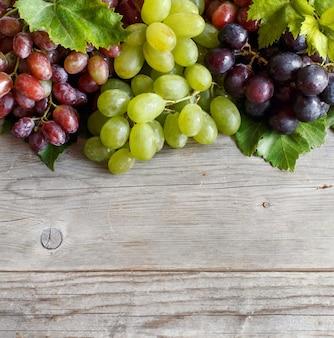Uvas vermelhas, brancas e azuis com folhas em uma velha mesa de madeira