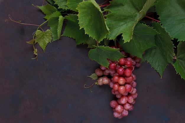Uvas vermelhas com folhas.