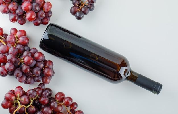 Uvas vermelhas com garrafa de vinho espalmadas sobre um fundo branco
