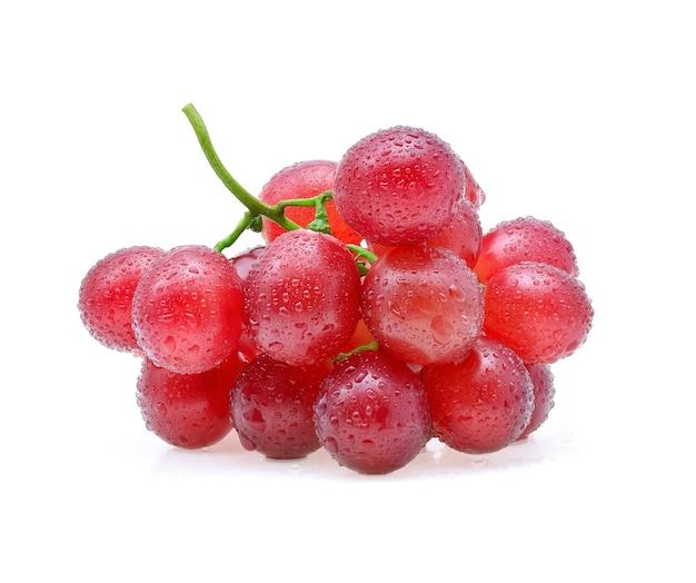 Uvas vermelhas com gota de água isolada no branco.