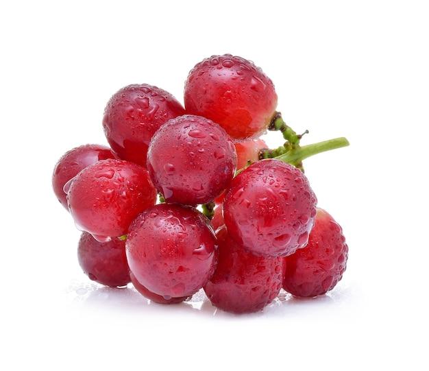 Uvas vermelhas com gotas de água isoladas no fundo branco.
