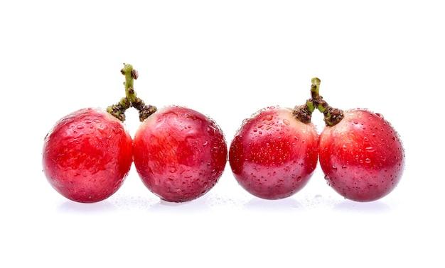 Uvas vermelhas com gotas de água isoladas no fundo branco