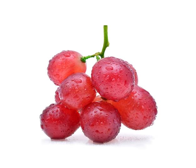 Uvas vermelhas e gotas de água isoladas no branco