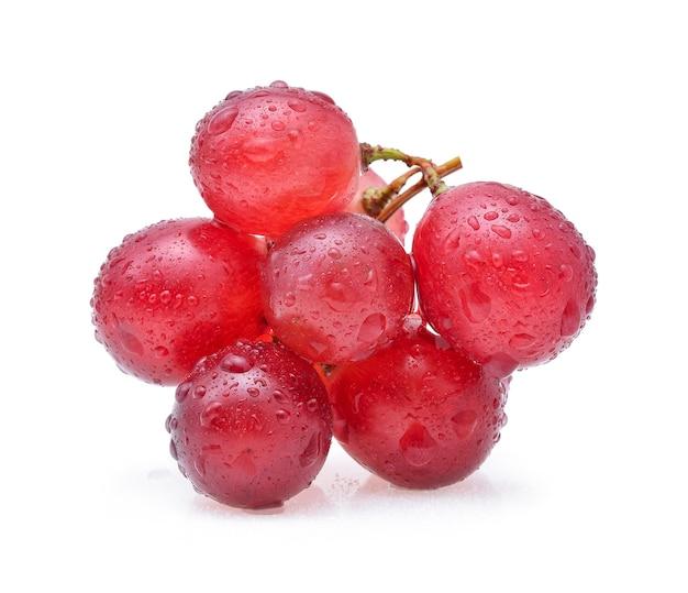 Uvas vermelhas e gotas de água isoladas no fundo branco