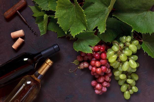 Uvas vermelhas e verdes com folhas, cortiça, saca-rolhas e duas garrafas de vinho, branco e vermelho.