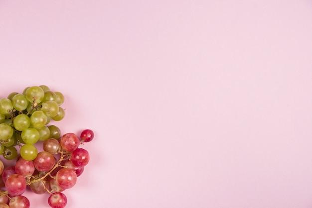 Uvas vermelhas e verdes no canto do fundo rosa