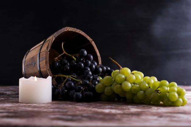 Uvas vermelhas e verdes saem de um balde de madeira
