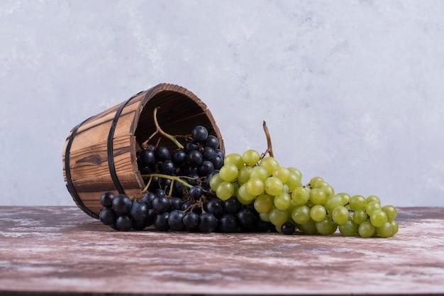 Uvas vermelhas e verdes saem de um balde de madeira.