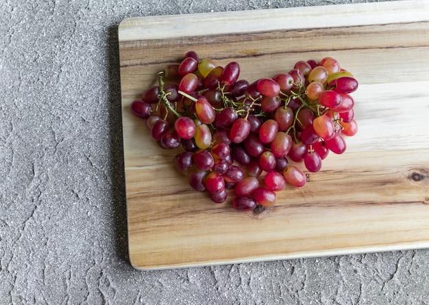 Uvas vermelhas em forma de coração no fundo de madeira