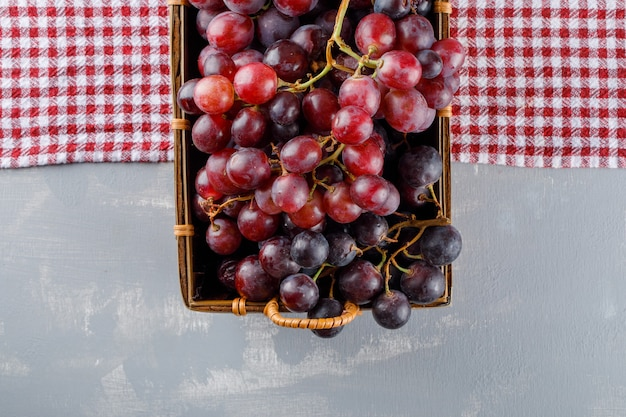 Uvas vermelhas em uma cesta plana sobre uma toalha de piquenique e gesso