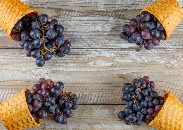 Uvas vermelhas escuras em cestos de vime em fundo de madeira, plana leigos.