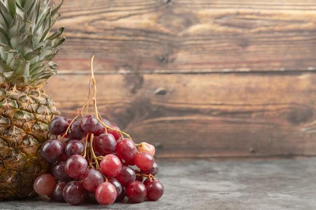 Uvas vermelhas frescas com abacaxi maduro na superfície de mármore.