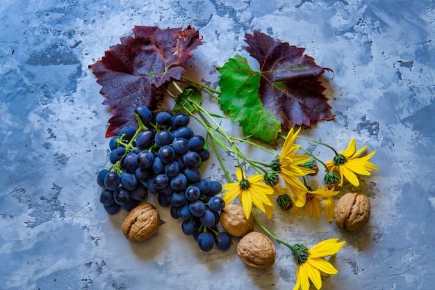 Uvas vermelhas frescas com flores e nozes na mesa de pedra.