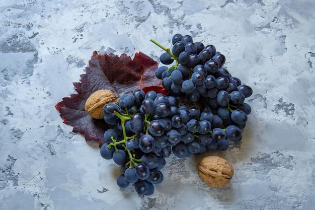 Uvas vermelhas frescas e nozes na mesa de pedra.