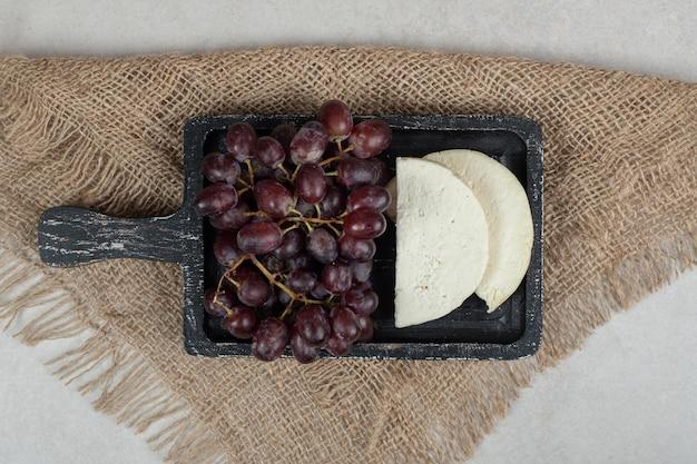 Uvas vermelhas frescas e queijo branco no quadro negro