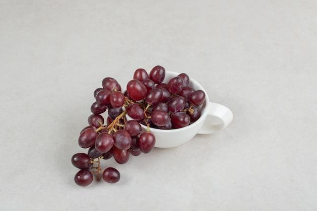 Uvas vermelhas frescas em copo branco.