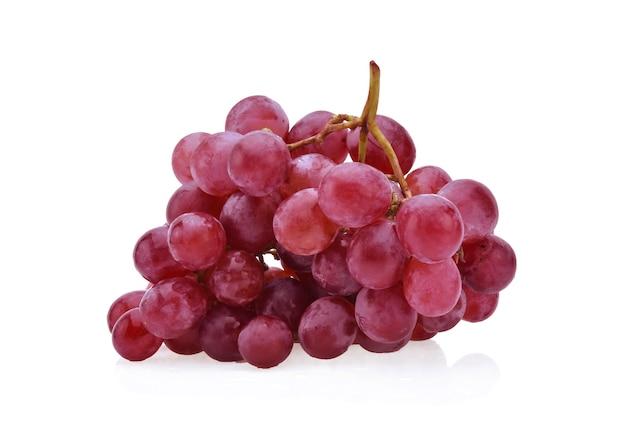 Uvas vermelhas isoladas na superfície branca.