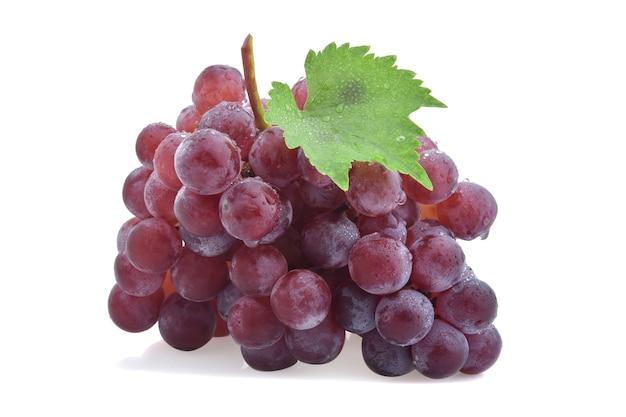 Uvas vermelhas maduras com folhas isoladas