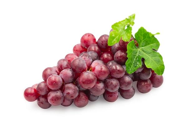 Uvas vermelhas maduras com folhas no fundo branco