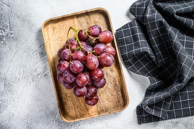 Uvas vermelhas maduras em uma tigela de madeira