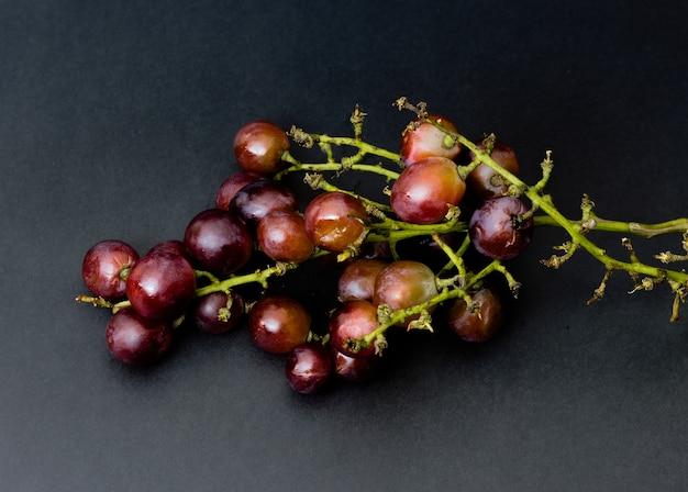 Uvas vermelhas podres isoladas na superfície preta
