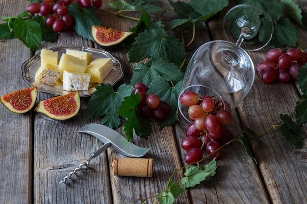 Uvas vermelhas, uma garrafa de vinho, figos, um copo, queijo, um saca-rolhas e uma rolha de vinho