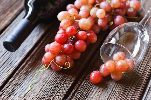 Uvas vermelhas, vidro, garrafa de vinho tinto, cortiça e saca-rolhas
