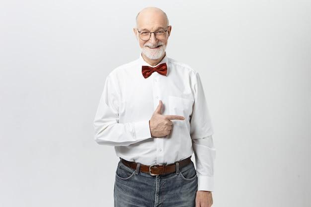 Vá por este caminho. alegre simpático pensionista masculino em roupas elegantes, apontando o dedo indicador, mostrando como chegar ao museu. homem sênior atraente indicando parede com copyspace para seu texto