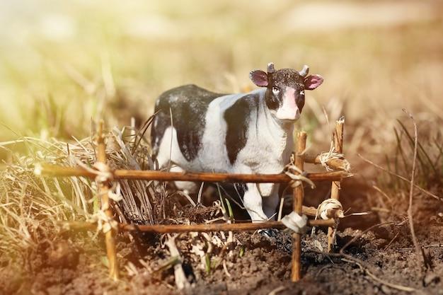 Vaca de brinquedo fotografada na rua com uma cerca de galhos no chão na grama
