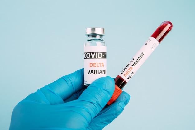Vacid 19 delta variante vacina e teste de sangue na mão sobre fundo azul. vacinação contra coronavírus