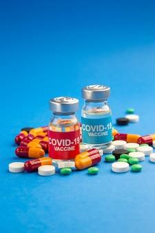 Vacina covid vista frontal em frasco pequeno com pílulas diferentes sobre fundo azul