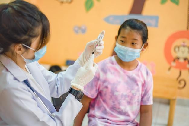 Vacinação contra o coronavírus. vacina para o covid19. médico dando vacinas em escolares na escola para prevenir uma grave epidemia entre os escolares. garotinho tomando vacina contra a gripe. prevenção contra o vírus.