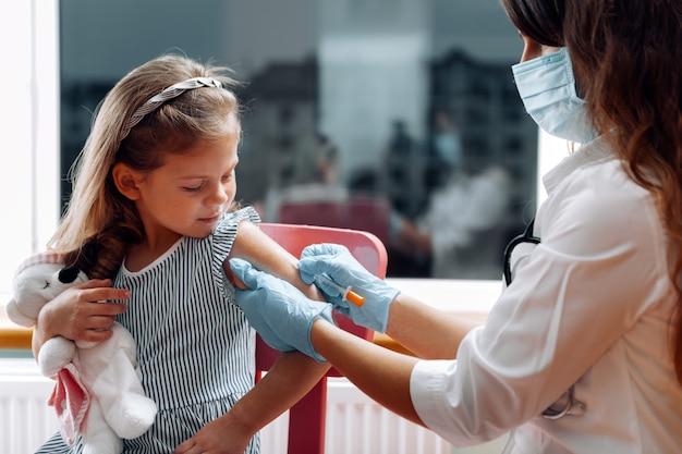 Vacinação de crianças. médico examinando uma criança em um hospital. covid-19