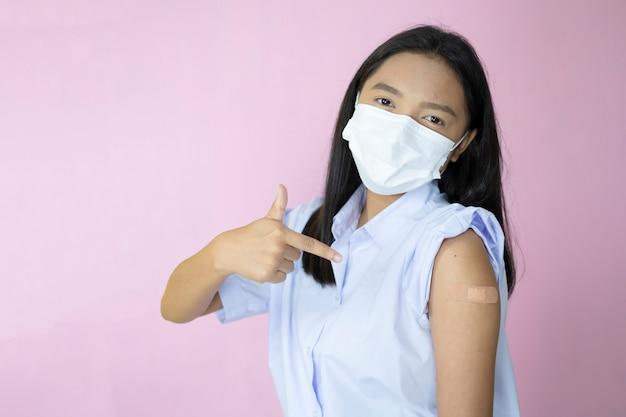 Vacinação de estudante asiático em fundo rosa.